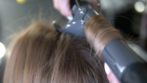woman using curling iron on hair